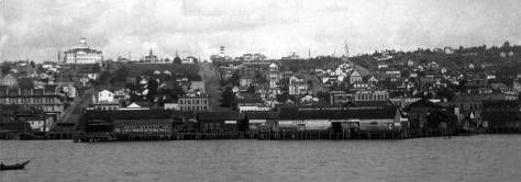 Looking back at Seattle from Elliot Bay early in 1887-88.  The Yesler Wharf that elbows thru the scene will be turned to a stubble of pilings by the Great Fire of June 6, 1889.  A year and a few week earlier Central School, the white box with tower on the left horizon at 6th and Madison, would by consumed by fire.  Columbia Street runs up to First Hill near the center of the panorama.