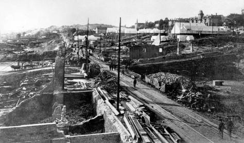 An unidentified photographer has climbed a ruin on the west side of Front Street (First Ave.) to look north along the waterfront following the Great Fire of 1889.  The already filled street ends on Columbia and Marion are evident just north or beyond the ruins.
