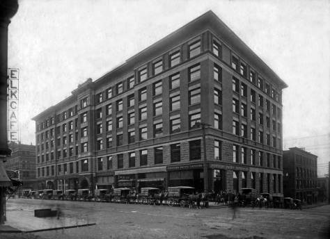 The Colman building at the southwest corner of Marion and Columbia with the Augustine and Kyer storefront near the middle  of the block and the store's delivery buggies posing in front.  (Courtesy, MOHAI)