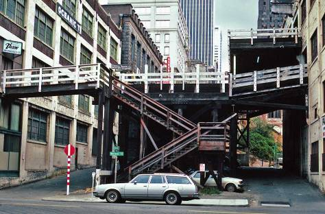 THEN: Following the city's Great Fire of 1889, a trestle was built on University Street, between Front Street (First Avenue) and Railroad Avenue (Alaskan Way). By the time Lawton Gowey photographed what remained of the timber trestle in 1982, it had been shortened and would soon be razed for the Harbor Steps seen in Jean Sherrard's repeat. (Courtesy Lawton Gowey)
