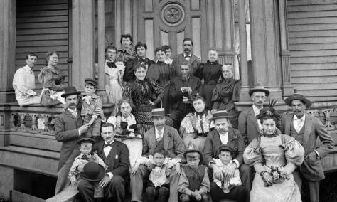 THEN: A mix of workers, friends and guests pose together on the front porch of Sarah Frances Baker's hotel at the northeast corner of Third Avenue and Marion Street in 1895.  Built ten years earlier by Martin and Elisabeth Stacy as their first mansion, the warring couple never lived in it.  Used in the early 1890s by the Seattle Chamber of Commerce, followed by Baker and her hotel, the Second Empire styled mansion's last tenant was the Maison Blanc Restaurant, which was closed by fire in 1960.  (Courtesy, Museum of History and Industry)