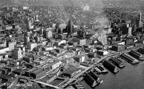 """The Municipal Market building can be found in this early 1930s aerial by first finding the armory building near the lower-left corner (just above the """"Wn."""" in the photo's own caption) and moving from the armory up and to the right.  There's the show-box shaped Municipal Market Building and its bridge over Western Ave. to the long row of Market stalls on the west side of Pike Place.   Note the long gaps parallel to the bay in Railroad Avenue.  The 1934-36 seawall construction has not started.  Harborview hospital, 1930, is on the First Hill horizon."""