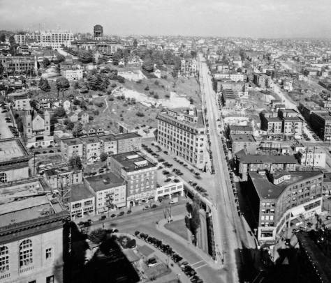 On the horizon Harborview Hospital is under construction and the top of King County's abandoned courthouse has been removed in prelude to it razing. This 1930 look from the Smith Tower also shows off the barren or cleared acres top-center and behind the flat-iron shaped 400 Yesler Building at the center. Our Lade of Good Help is on the left.