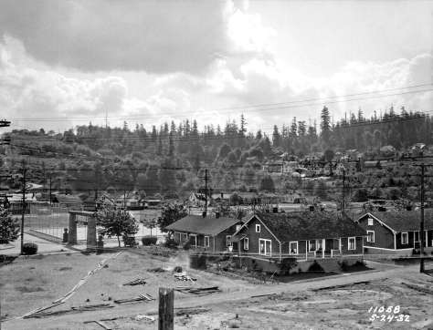 THEN: Looking southeast from above Alki Avenue, the Schmitz Park horizon is serrated by the oldest trees in the city. The five duplexes clustered on the right were built 1919-1921 by Ernest and Alberta Conklin. Ernest died in 1924, but Alberta continued to live there until well past 1932, the year this photograph was recorded. (Seattle Municipal Archives.)