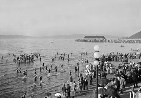Looking northeast from the observation portico on the roof of the Bath House. The long dock and building, upper-right, was a short-lived whaling station. Luna Park is seen further to the right below Duwamish Head. Magnolia is on the left horizon and Queen Anne Hill (buth humps of it) on the center-right horizon and over the whalers.