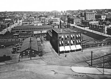 Here, circa 1909, we can find both the featured Row, far right, and the Electric Company plant filling most of the mid-ground subject. Westlake Ave. is here cut through the neighborhood at the bottom. Capitol Hill is on the east horizon, with Broadway High School at the center. The car barns on the right at the northeast corner of Fifth Avenue and Pine Street have not yet been remodeled for the Westlake Market, which can be found in the photo that follows this one.
