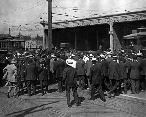The west facade of the North Seattle yard near or during the end of the 1917 trolley strike. The workers - we assume - are standing on Fifth Avenue. The structures to the left of the garage are on the north side of Mercer Street. (Courtesy, the Museum of History and Industry)