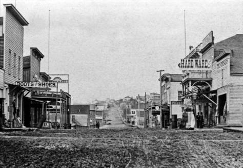 The same Front Street but earlier, about 1880. Front shows here the graded swoop of its improvement from 1876.