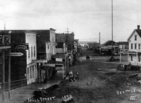 The Kellogg box can be identified by its balcony in this 1874 look west on Mill Street from Second Avenue. The Occidental Hotel is on the right, now home for the Sinking Ship Garage. Yesler's second Mill appears on the distant right beyond the civic flag pole in set in the middle of Pioneer Place.