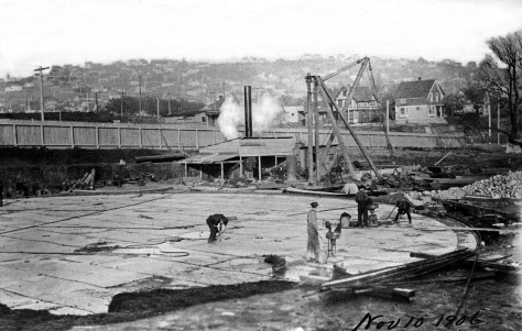 "The foundation for the first of two tanks, with the Queen Anne Hill horizon, as yet without Queen Anne High School (1909). This snapshot like most of the others in the ""Gas Album"" is dated. Nearly a half year before the feature photo, this is November 10, 1906."