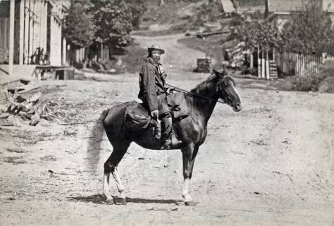 THEN: Pioneer mailman Dutch Ned poses on his horse on Cherry Street. The ca. 1880 view looks east over First Avenue when it was still named Front Street. (Courtesy: The Museum of History and Industry, aka MOHAI)