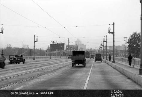 Looking north on the University Bridge from near the bascule. Nov. 9, 1933. The address at the base of the photo's own caption refers to the billboard at the scene's center, and not the photographer's prospect. This is another Foster-Kleiser photo. Might that be the photographer's coupe on the far left, with the open door?