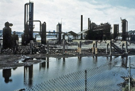 "THEN: The 1906-07 Gas Works at the north end of Lake Union went idle in 1956 when natural gas first reached Seattle by pipeline. In this photo, taken about fifteen years later, the Wallingford Peninsula is still home to the plant's abandoned and ""hanging gardens of metal."" (Courtesy: Rich Haag)"