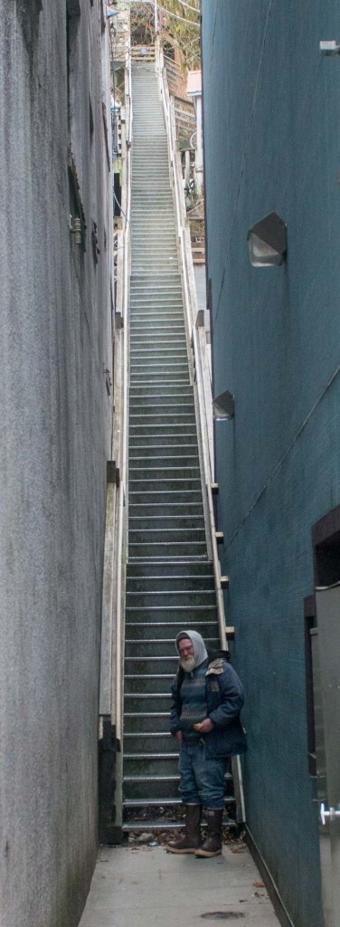 A citizen of Juneau contemplates one of many stair climbs leading out of the central business district
