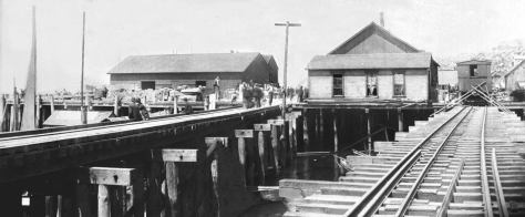 This rare record looks north on the two railroad trestles - the Seattle Lake Shore and Eastern on the left and the Ram's Horn, on the right, that survived from this point north the city's Great Fire of June 6, 1889, with the splashing work of bucket lines. The Schwabacher Wharf seen here, thereby survived to serve in the early rebuilding of the ruined business district and the waterfront, which from this point south was consumed to the water-line.
