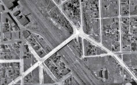 "This 1936 aerial for mapping centers on the nearly new Albro Place bridge that crossed above the wide swath of railroad tracks and replaced the ground level plank-paved crossing on Graham Street. The remnants of this last can be detected as a lighter-shade of covering a little less than a block south (right) of the overpass. The disturbed ground cover on Juneau Street, which support the pedestrian overpass into Georgetown can also be ""sensed"" to the north (left) of the Albro Bridge, about one long block distant. Half of the Seattle Electric Company's gas tank is revealed at the photo' s bottom-right corner. Part of the brewery shows at the upper-left corner. (Courtesy: Museum of History and Industry)"