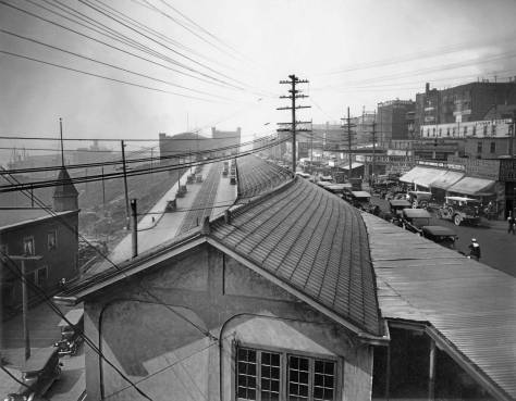 THEN: A circa 1920 look north along the tiled roofline of the Pike Place Market's North Arcade, which is fitted into the slender block between Pike Place, on the right, and Western Avenue, on the left. (Courtesy, Museum of History and Industry)