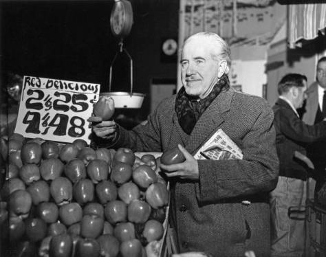 THEN: Mark Tobey, almost certainly Seattle's historically most celebrated artist, poses in the early 1960s with some Red Delicious apples beside the Sanitary Market in the Pike Place Market. (Courtesy, Museum of History and Industry)