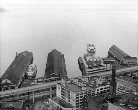 "Wade Stevenson's looks to the waterfront from the Smith Tower observatory circa 1959. Here the Kalakala is docked in t he slip between Pier 2 and 2, the ""Alaska Piers."" The Grand Trunk Pier, far right, is still in place. One of the ferries purchased from San Francisco Bay following the construction their of the suspension bridges, appreoached Colman Dock."