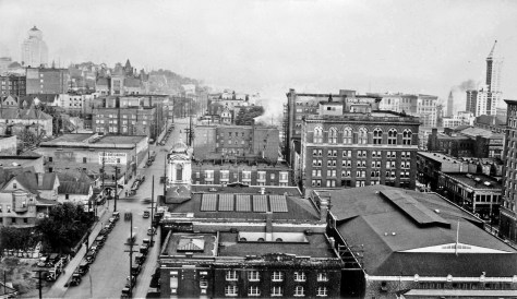 Looking south with Sixth Ave. on the left and Fifth on the right. Landmarks include Plymouth Congregational Church, the Y.W.C.A., the Smith Tower, far right, and Harborview Hospital on the far-left horizon.