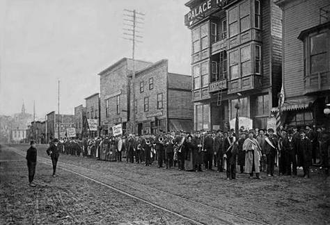 """The Salvation Army band posing on Jackson Street in front of the Palace Theatre, possibly during or following a """"battle of the bands"""" with the house orchestra. The subject looks east from Commercial Street (First Ave. S.)."""