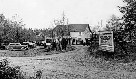 THEN: Before it became a city park, Licton Springs was run as a health spa. The distant home, left-of-center, at the northeast corner of N. 97th Street and Densmore Avenue N., survives in Jean Sherrard's repeat. It can be found on the left above the Y in the Licton Springs Park pathway. (Courtesy, Seattle Municipal Archives)