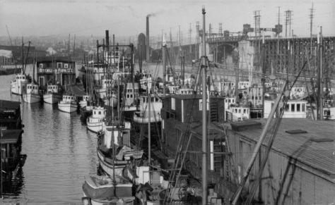 Ballard's bascule bridge on 15th Ave. n.w. seen over the masts & stacks of Fishermen's Terminal.