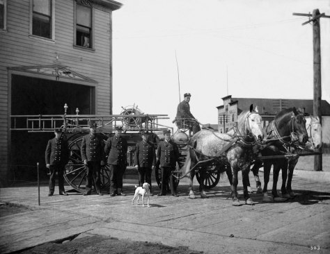 THEN: Ballard's short-lived fire station at the southwest corner of Broadway (NW Market Street) and Burke Avenue (Russell Ave. NW) circa 1903. Looking northwest the view includes, above the horses, a glimpse of Sypher's Hall, a rentable venue for playful and/or political events. (Courtesy, Museum of History and Industry)