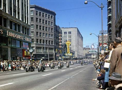 THEN: Lawton Gowey looks north through the tail of the 1957 Independence Day Parade on Fourth Avenue as it proceeds south through the intersection with Pike Street. (Courtesy, Lawton Gowey)