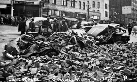 Rubble from the 1949 earthquake. The subject looks south on the Second Avenue Extension from its southwest corner with Yesler Way. The southwest facade of the Chin Gee Hee Building rises with its six windows above the damaged swept-back auto parked on the right.