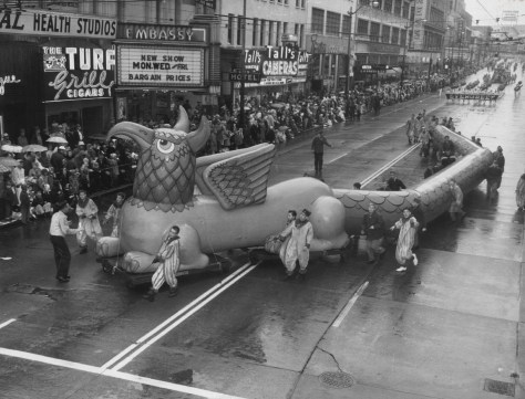 "The parade heading south on Third Ave., reaches Union Street and a line-up of the then popular Turf Club, the Embassy Theatre and Talls Cameras. The Evergreen High School band follows. The Times caption reads, ""Mythical Monster: A crew of Boy Scouts struggled valiantly to control a 110-foot griffin balloon, which wound its way along Third Avenue near Union Street in yesterday's parade. It took 50 Scouts, working in 25-member teams, to guide the griffin."""