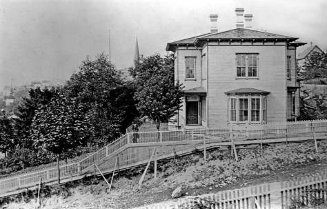 The Leary/Weed home with a large front lawn at the Northeast corner of Madison Street and Second Avenue. Mayor aka Dr. Weed poses behind the fence.