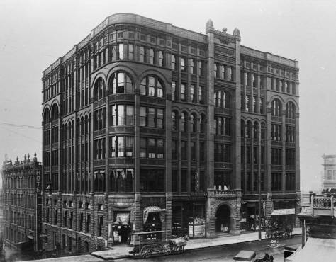 Click-Click to enlarge and find the glasses hanging outside the second floor window above-left of the arched entrance to the Burke Building. Also note the Har