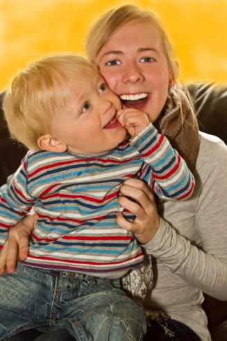 blond mother laughing holding a child in striped shirt and jeans