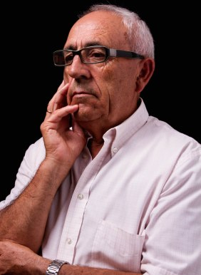 older man white hair and shirt with black rimmed glasses thoughtful