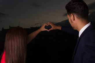 couple making a heart with their hands against a black background