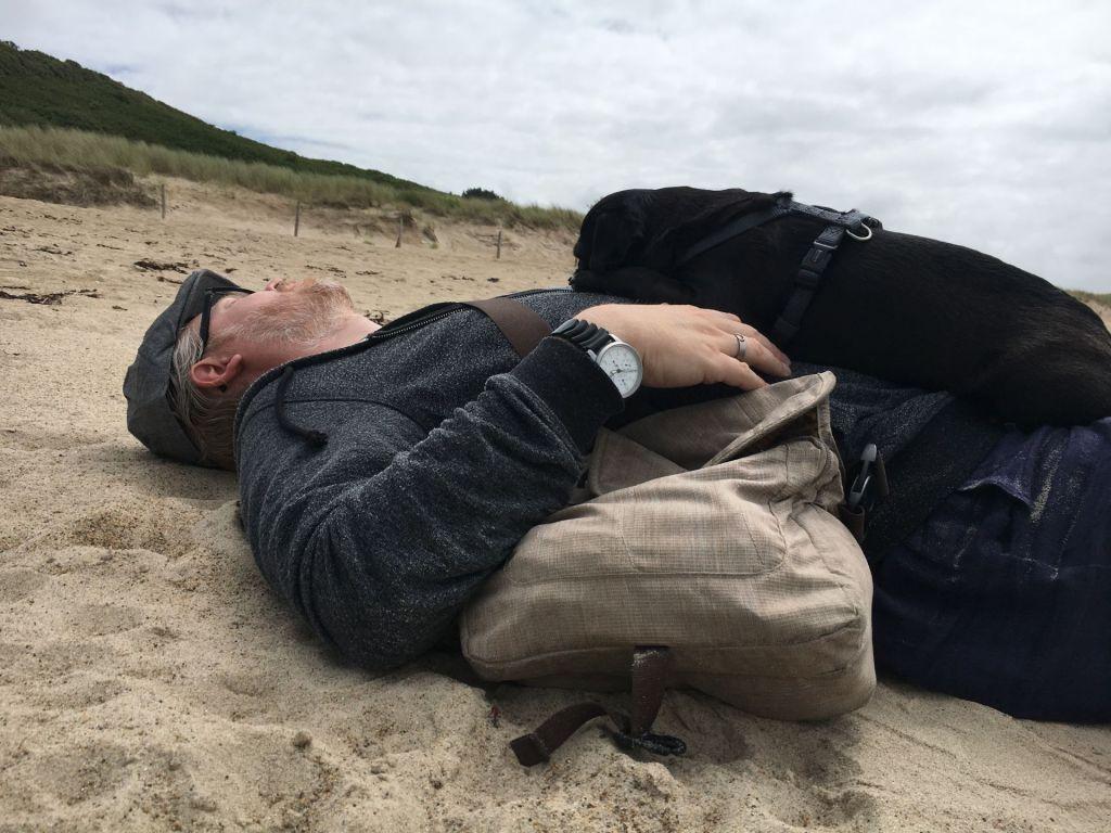 Herrchen und Mops schlafen am Strand