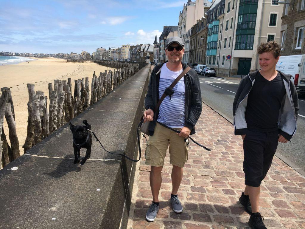 Pauli läuft lässig auf der Mauer am Strand von St. Malo