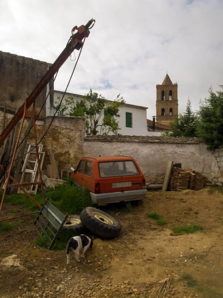 Coche antiguo naranja con chatarra al rededor y la torre de Granja de Torrehermosa al fondo