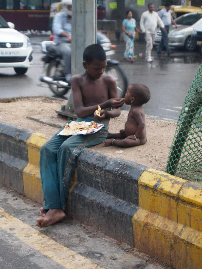 Un chico le da de comer a un bebé en mitad del tráfico en Jaipur