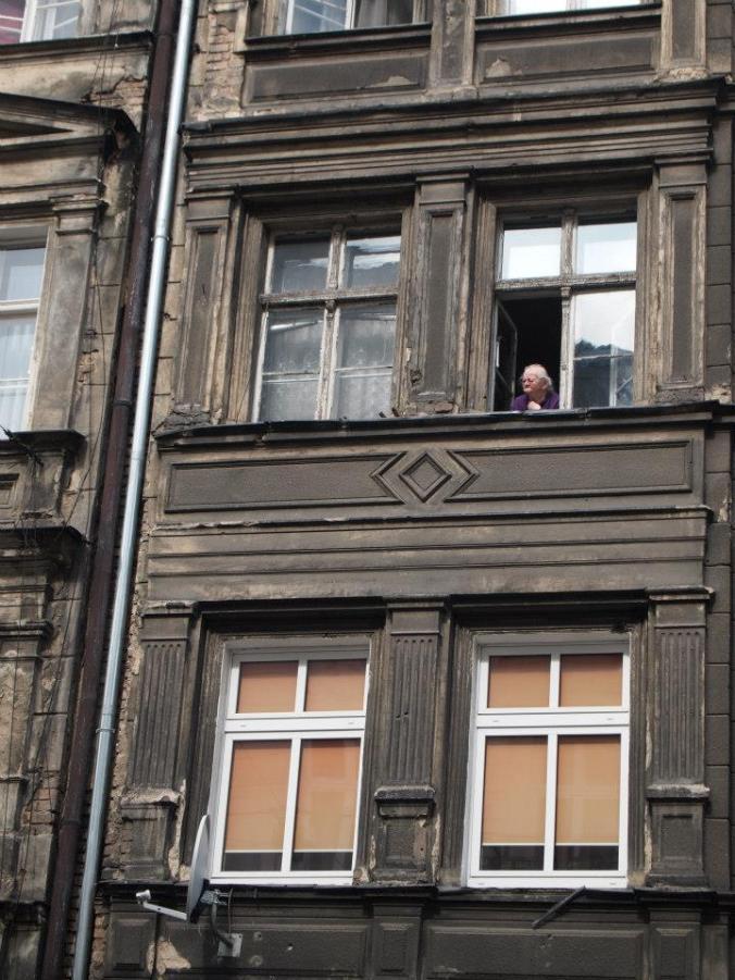 Mujer asomada a la ventana de un edificio antiguo en Poznan
