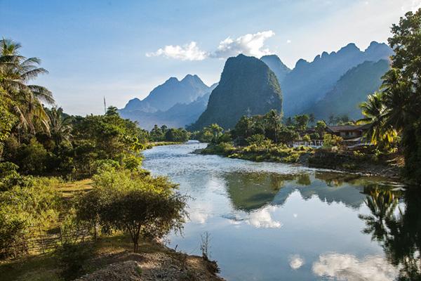 Eine majestätische Bergwelt spiegelt sich in der Abendsonne am Nam Song Fluss in Vang Viengj