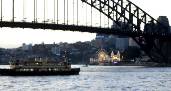 Dusk on Sydney Harbour, as Luna Park lights up.