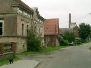 Straßenszene, im Hintergrund Gutsgebäude