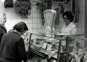 Alltag im Paulinenauer Konsum. Das Bild aus dem Paulinenauer Institutsarchiv stammt vermutlich aus den 1980er Jahren. Es zeigt den Fleischstand, der von Frau Konrad betreut wird. Frau Zeglin wählt aus dem reichlichen Angebot. Rechts im Bild: der Brötchenstand.
