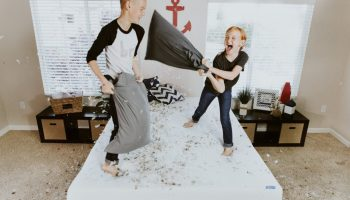 Kids playing with pillows on a bed