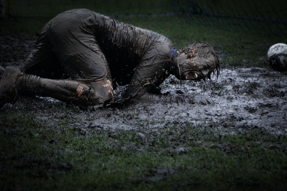 Man lying on grass, covered in mud