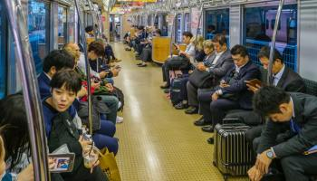 People staring at their devices in a busy train
