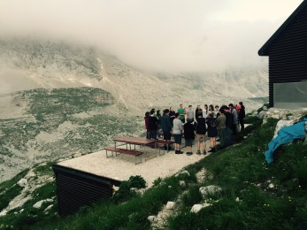Young hiking group sing hymn, Zasavska koća, Triglavski National Park
