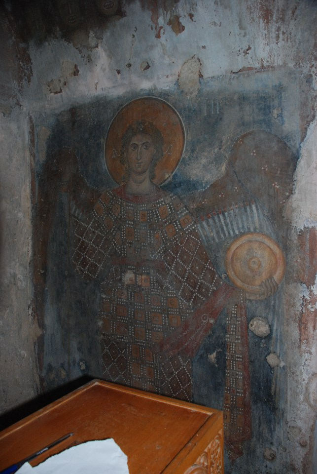 Fresco of the Archangel Michael. The pen and scrap of paper are for recording donations. Photograph by Paul Nettleton